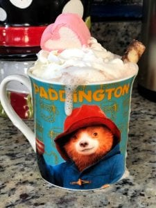 paddington mug of hot chocolate with overflowing whipped cream and a marshmallow