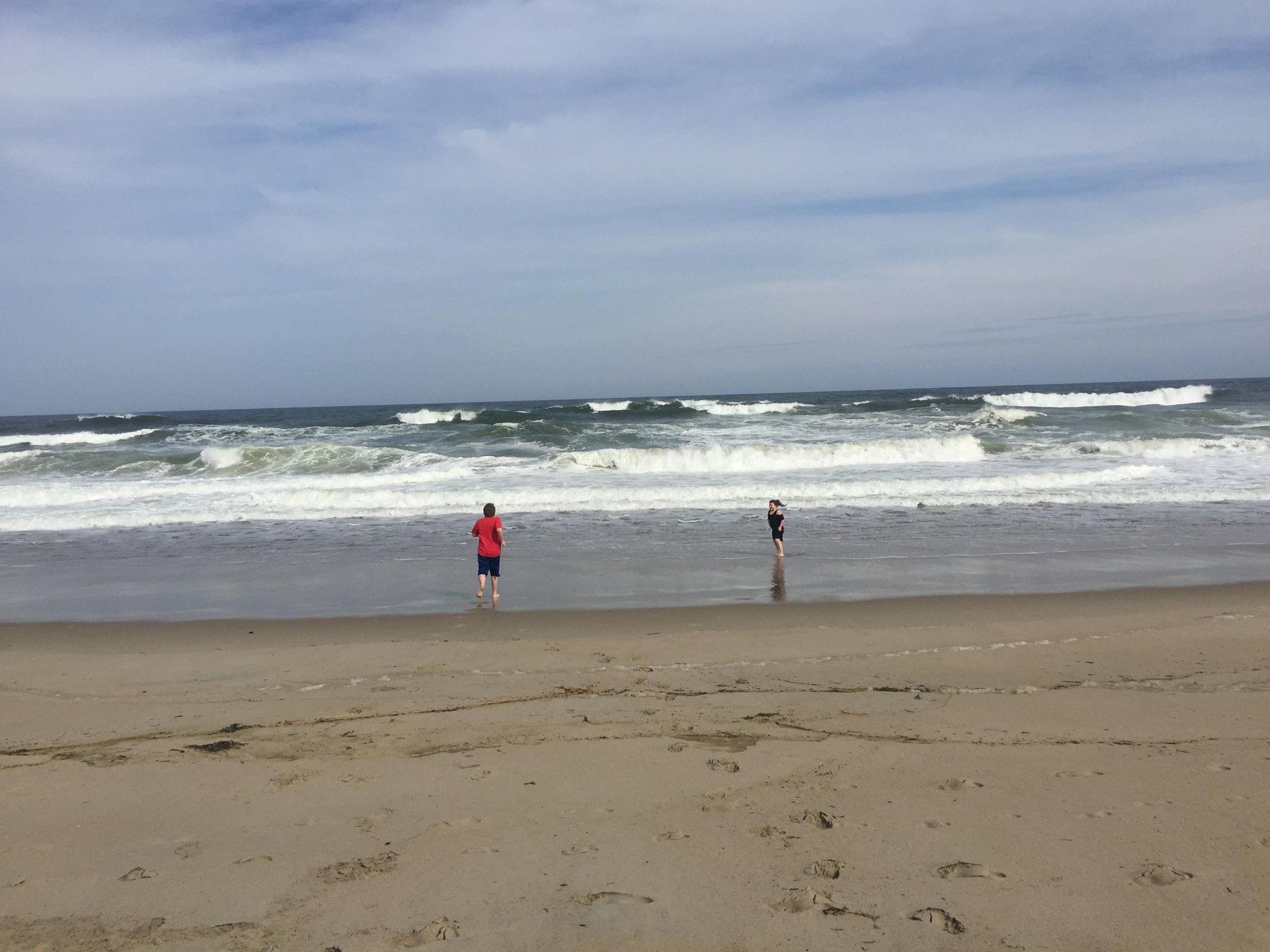 image of children running into ocean